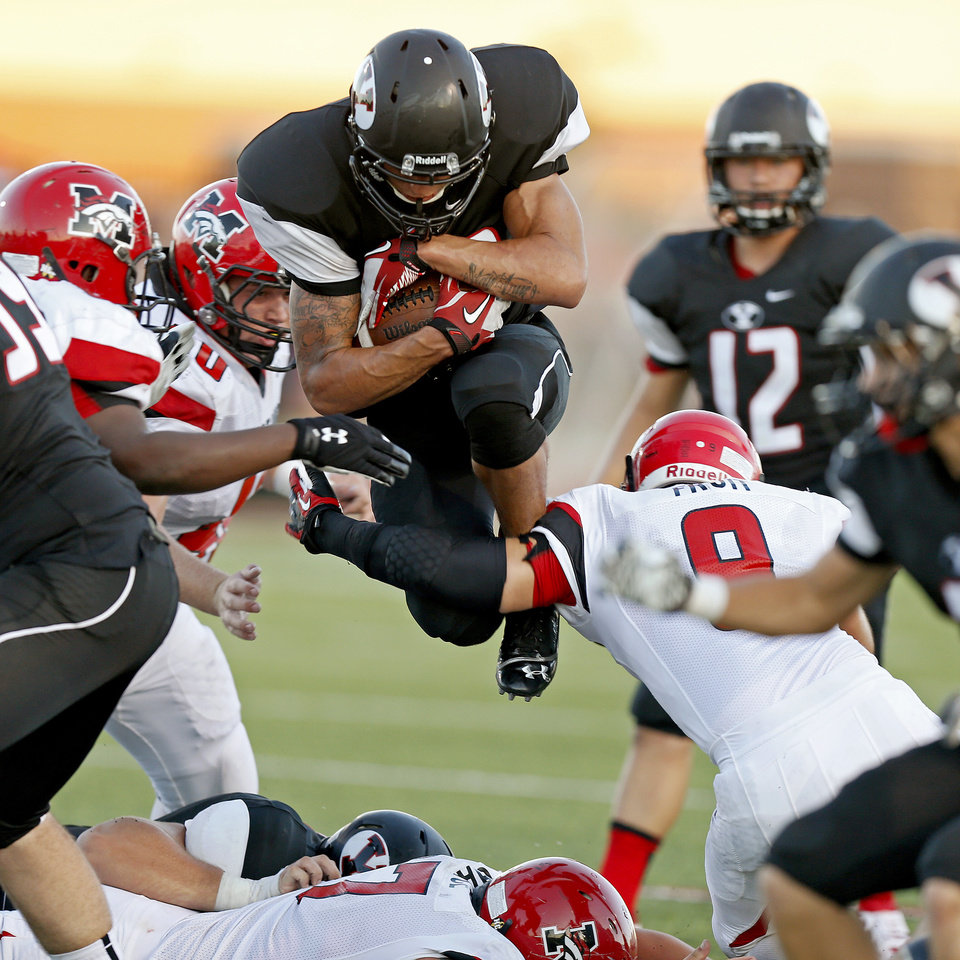 Photo - Yukon's A.J. West tries to leap past Mustang's Steven Fruit, at right, during a high school football game in Yukon, Okla., Friday, August 31, 2012. Photo by Bryan Terry, The Oklahoman