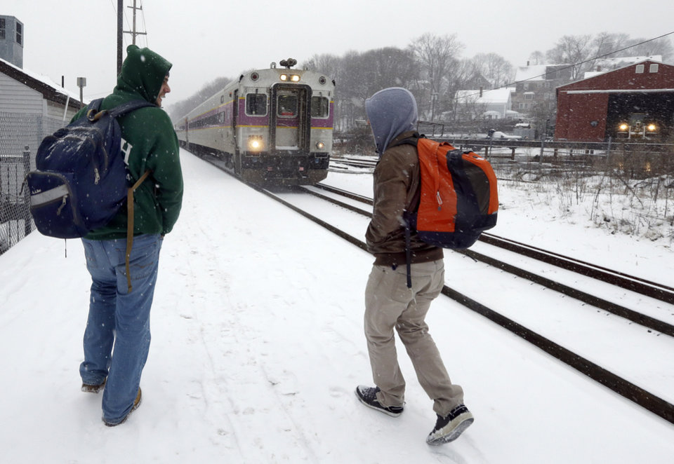 Photo - Two travelers walk to catch the last train into Boston from the Andover, Mass. train station as snow falls on Friday, Feb. 8, 2013. A major winter storm is barreling into the U.S. Northeast with up to 2 feet of snow expected for a Boston-area region that has seen mostly bare ground this winter. The MBTA will suspend all transit service in the late afternoon due to the storm. (AP Photo/Elise Amendola)