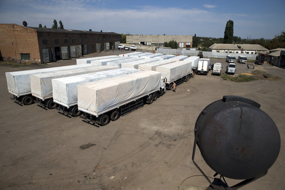 Photo - Trucks painted white and forming part of an aid convoy are parked close to a border control point with Ukraine in the Russian town of Donetsk, in the Rostov-on-Don region, Russia, Sunday, Aug. 17, 2014. Fighting in Ukraine has escalated since the insurgency arose in April, with government troops steadily taking back rebel-held territory in the east. (AP Photo/Pavel Golovkin)