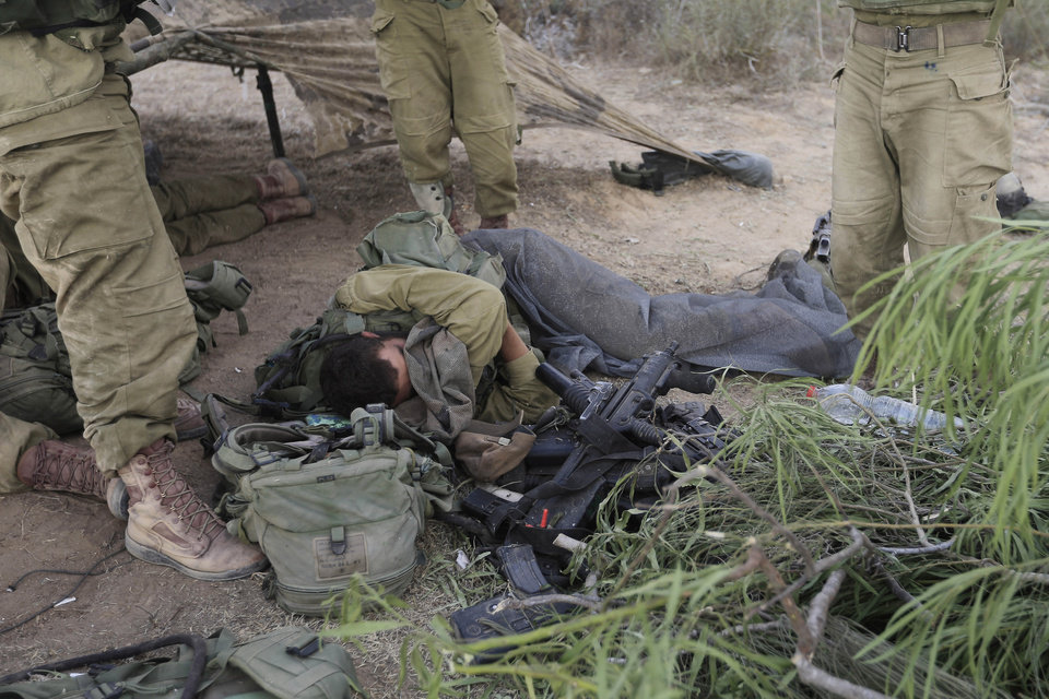 Photo - An Israeli soldier sleeps near the border of Israel and the Gaza Strip Wednesday, July 23, 2014.  Israeli troops battled Hamas militants on Wednesday near a southern Gaza Strip town, sending Palestinian residents fleeing, as the U.S. secretary of state presses ahead with top-gear efforts to end the conflict that has killed hundreds of Palestinians and tens of Israelis.(AP Photo/Tsafrir Abayov)