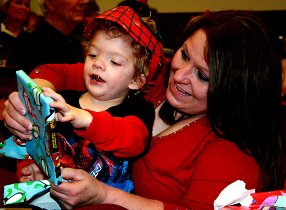 Landen Hall, 4, sporting a Spider-Man mask he just received, opens another present at the J.D. McCarty Center's annual Christmas party Sunday as his mother, Shellie Hall, looks on. PHOTOS BY LYNETTE LOBBAN, FOR THE OKLAHOMAN