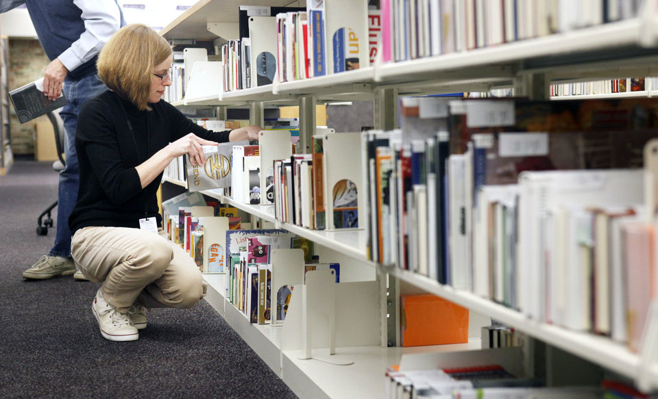 Library Aide Jessica Little shelves reserved books as a part of the new self-serve reserve system at the Edmond branch of the Metropolitan Library System in Edmond, OK, Friday, Feb. 17, 2012. By Paul Hellstern, The Oklahoman