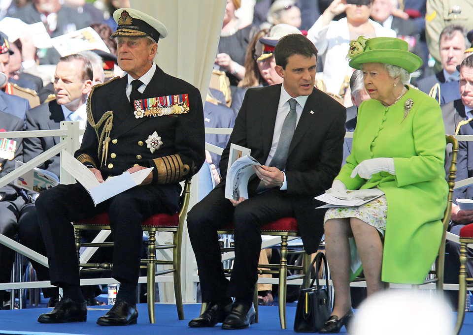 Photo - Britain's Prince Philip, French Prime Minister Manuel Valls and Britain's Queen Elizabeth II, from left, attend the Service of Remembrance, at the Commonwealth War Graves Commission Cemetery, in Bayeux, France Friday June 6, 2014, as part of the commemorations for the 70th anniversary of the D-Day landings. (AP Photo/Remy de la Mauviniere/Pool)