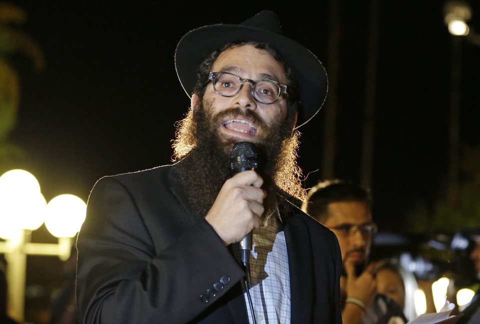 Photo - Rabbi Chaim Lipskier makes remarks to students and supporters taking part in a candle light vigil at the University of Central Florida, Wednesday, Sept. 3, 2014, in Orlando, Fla., to honor Steven Sotloff, the second American journalist to be beheaded by the Islamic State group in two weeks. Sotloff attended University of Central Florida between 2002 and 2004. (AP Photo/John Raoux)