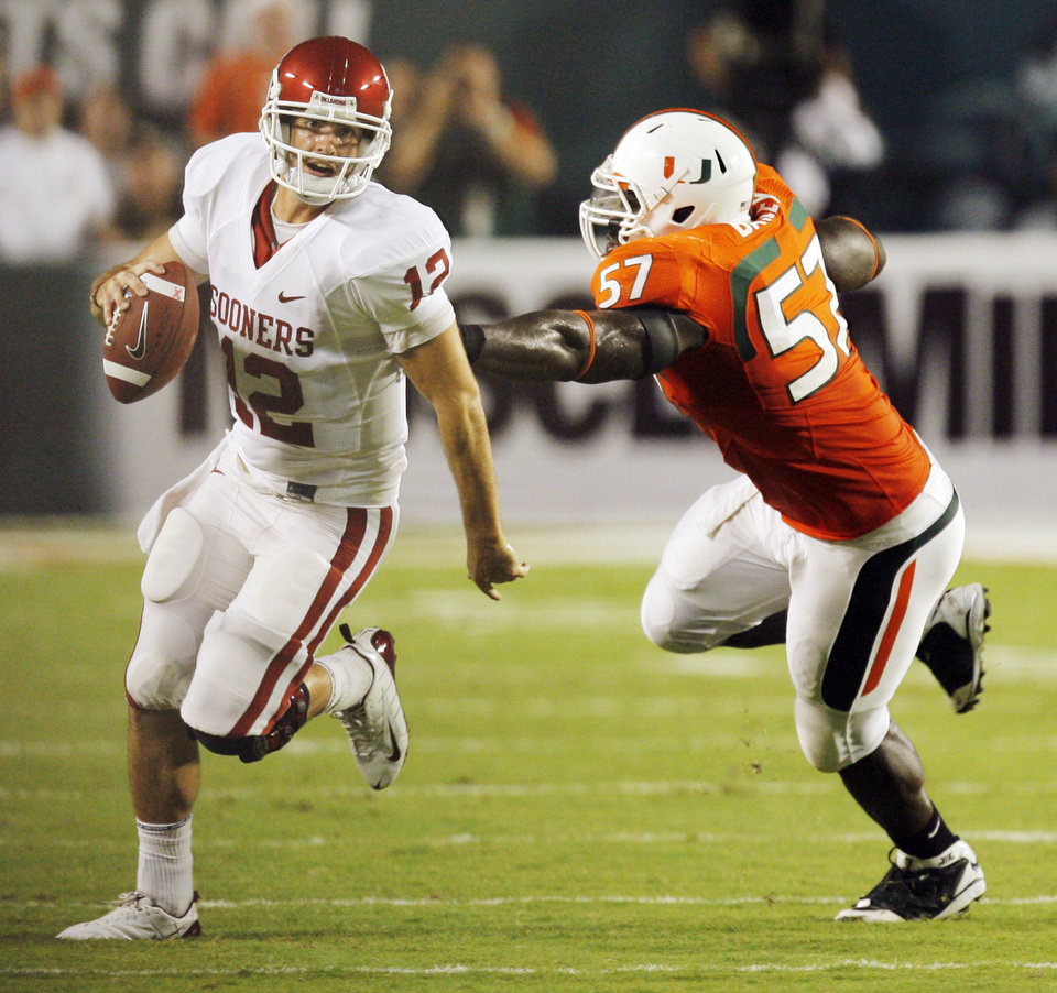 Photo - OU quarterback Landry Jones (12) scrambles away from Miami's Allen Bailey (57) on a fourth down play near the end of the second quarter during the college football game between the University of Oklahoma (OU) Sooners and the University of Miami (UM) Hurricanes at Land Shark Stadium in Miami Gardens, Florida, Saturday, October 3, 2009. Jones threw the ball away on the the play. Photo by Nate Billings, The Oklahoman