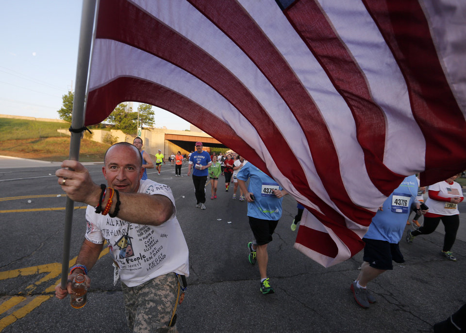Photo - A man carries and American flag on NE 4th St. during the Oklahoma City Memorial Marathon in Oklahoma City, Sunday, April 28, 2013.  Photo by Garett Fisbeck, For The Oklahoman