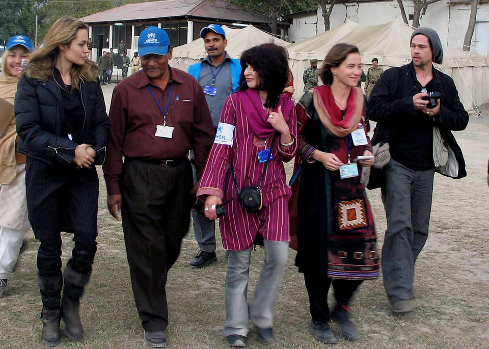 Photo - FILE - In this Saturday, Nov. 26, 2005, file photo, Hollywood actress and United Nations High Commissioner for Refugees Ambassador Angelina Jolie, left, and actor Brad Pitt, right, are escorted by unidentified UNHCR officials towards a helicopter in Muzaffarabad, Pakistan, after seeing an earthquake-affected area. Jolie and Pitt were married Saturday, Aug. 23, 2014, in France, according to a spokesman for the couple. (AP Photo/Roshan Mughal, File)