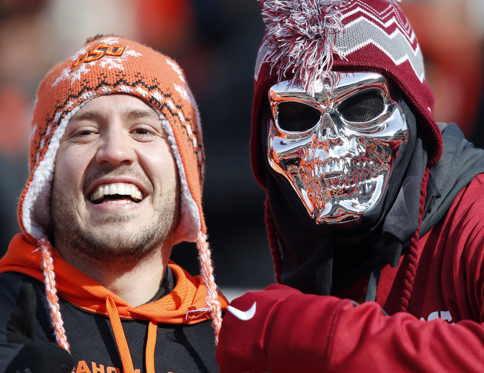 An OSU and an OU fan brave the cold during the Bedlam college football game between the Oklahoma State University Cowboys (OSU) and the University of Oklahoma Sooners (OU) at Boone Pickens Stadium in Stillwater, Okla., Saturday, Dec. 7, 2013. Photo by Chris Landsberger, The Oklahoman