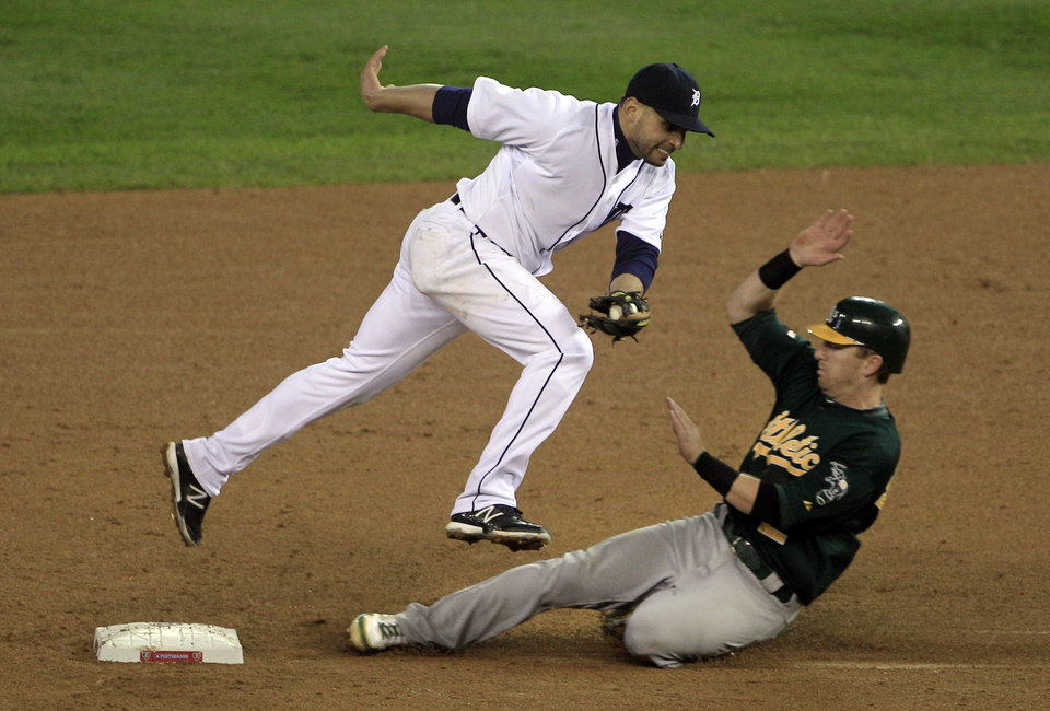 Detroit Tigers second baseman Omar Infante, top, jumps over Oakland Athletics' Cliff Pennington after forcing him out at second base on a fielder's choice during the fifth inning of Game 1 of the American League division baseball series, Saturday, Oct. 6, 2012, in Detroit. (AP Photo/Carlos Osorio)