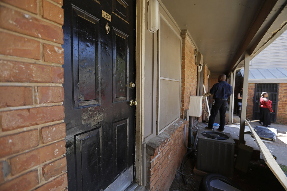 Photo - Workers repair a neighbor's front door, rear, blown off during a raid when FBI agents on Wednesday rescued Frank Arthur Janssen, of Wake Forest, N.C., from an apartment, foreground, in a housing complex in Atlanta, Thursday, April 10, 2014. John Strong, FBI special agent in charge in North Carolina, said Janssen's kidnapping was related to his daughter's prosecution of North Carolina prisoner Kelvin Melton, who is serving a life sentence for his 2012 conviction for being a habitual felon.  (AP Photo/David Goldman)