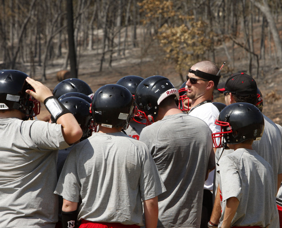 WILDFIRE / AFTERMATH / DAMAGE: Luther High School football coach Shawn Meek talks to his players on the practice field which was partially burned by recent wildfires in Luther, OK, Tuesday, August 7, 2012, By Paul Hellstern, The Oklahoman