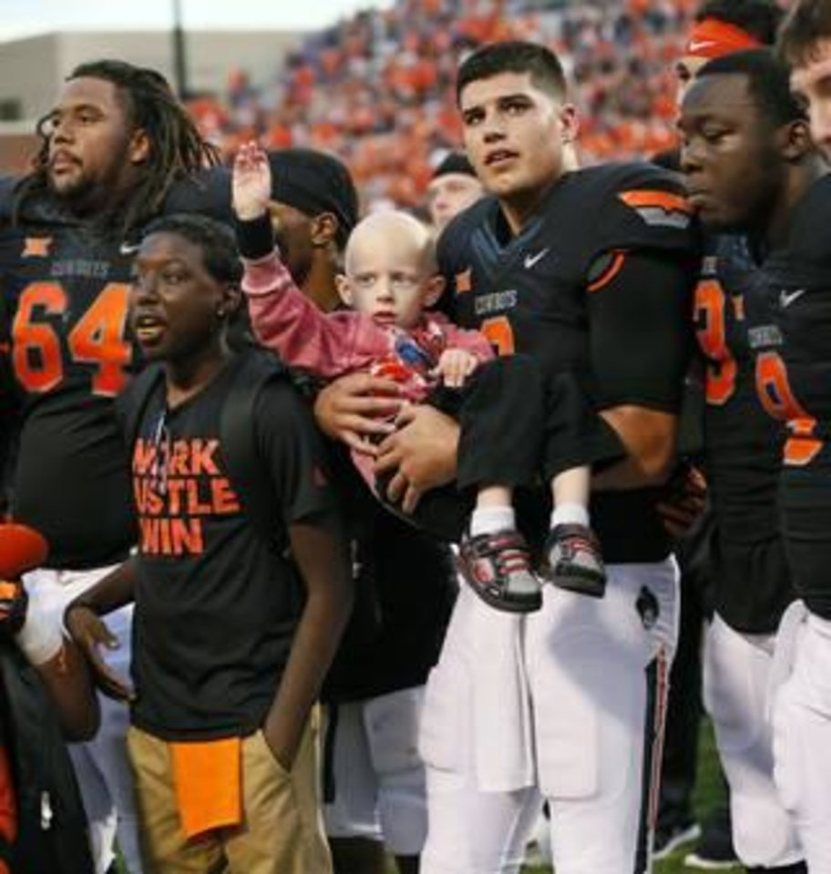 Photo - Oklahoma State quarterback Mason Rudolph holds Gavin following the Cowboys' 36-34 victory over Kansas State. Gavin attended the game with the Special Spectators, a nationwide program that provides game-day experiences for kids battling serious illness. [Photo by Nate Billings, The Oklahoman]