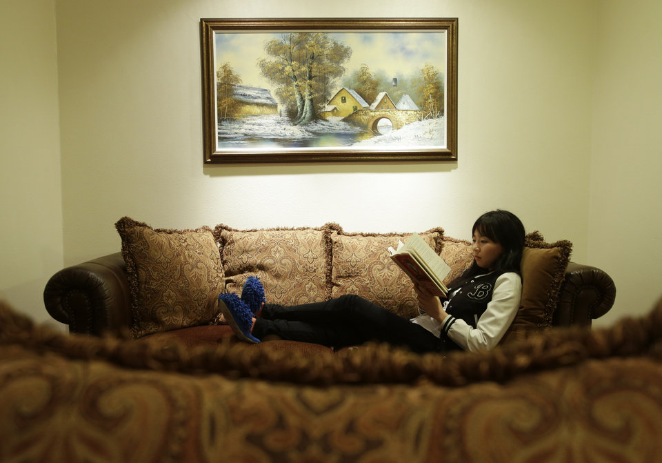 ADVANCE FOR USE MONDAY, MARCH 18, 2013 AND THEREAFTER - In this Monday, March 11, 2012 photo, Victoria Hu studies in the living room of their house in Rancho Palos Verdes, Calif. Victoria keeps her emotions in check when talking about her father. But then, as a teenager trying to find her way forward, she poured her feelings into letters to him, even an essay she wrote for a college application. (AP Photo/Chris Carlson)