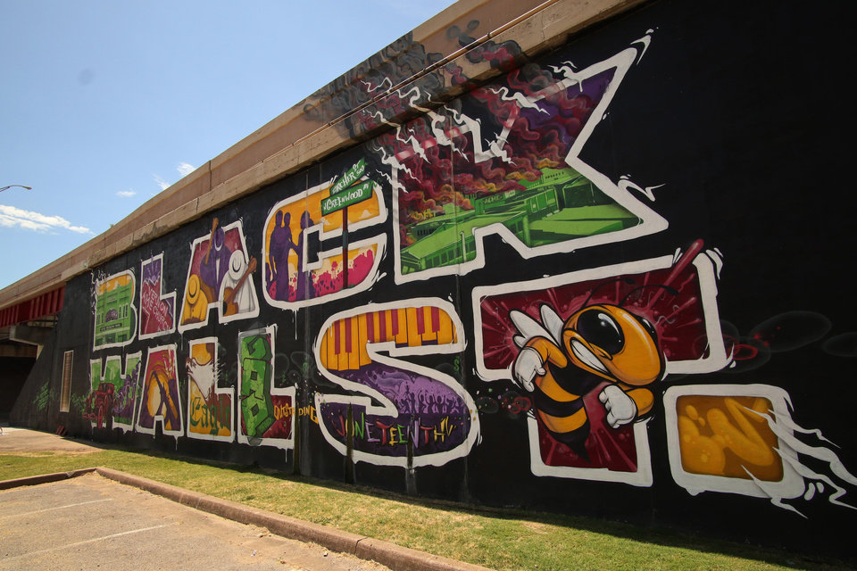 Photo - A Black Wall Street mural on the north side of I-244 highway that runs through the historic Greenwood District in North Tulsa, know at the time as the Black Wall Street, the site of a massacre of African Americans by a white mob, resulting in hundreds of deaths in 1921, in Tulsa Friday, June 12, 2020. [Doug Hoke/The Oklahoman]
