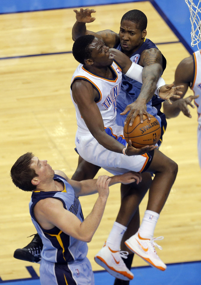 Photo - Oklahoma City's Reggie Jackson (15) drives to the basket as he is defended by Memphis' Ed Davis (32) and Beno Udrih (19) during Game 2 in the first round of the NBA playoffs between the Oklahoma City Thunder and the Memphis Grizzlies at Chesapeake Energy Arena in Oklahoma City, Monday, April 21, 2014. Photo by Sarah Phipps, The Oklahoman