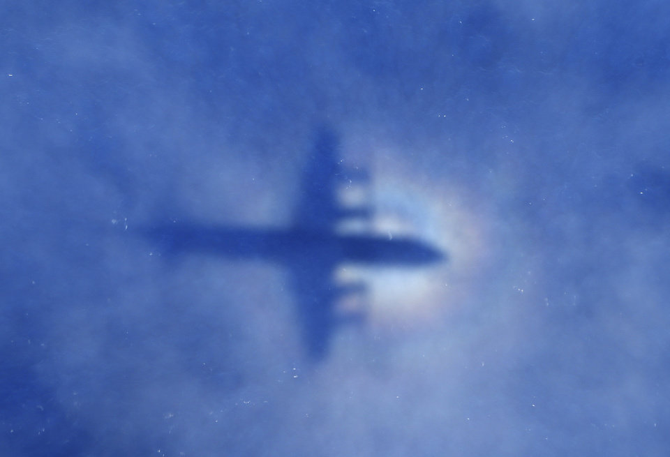 Photo - In this Monday, March 31, 2014 photo, a shadow of a Royal New Zealand Air Force P-3 Orion aircraft is seen on low cloud cover while it searches for missing Malaysia Airlines Flight MH370 in the southern Indian Ocean. Malaysia's national police chief has warned that the investigation into what happened to the plane may take a long time and may never determine the cause of the tragedy. Khalid Abu Bakar said Wednesday, April 2, that the criminal investigation is still focused on four areas — hijacking, sabotage and personal or psychologica problems of those on board the plane. (AP Photo/Rob Griffith, Pool)