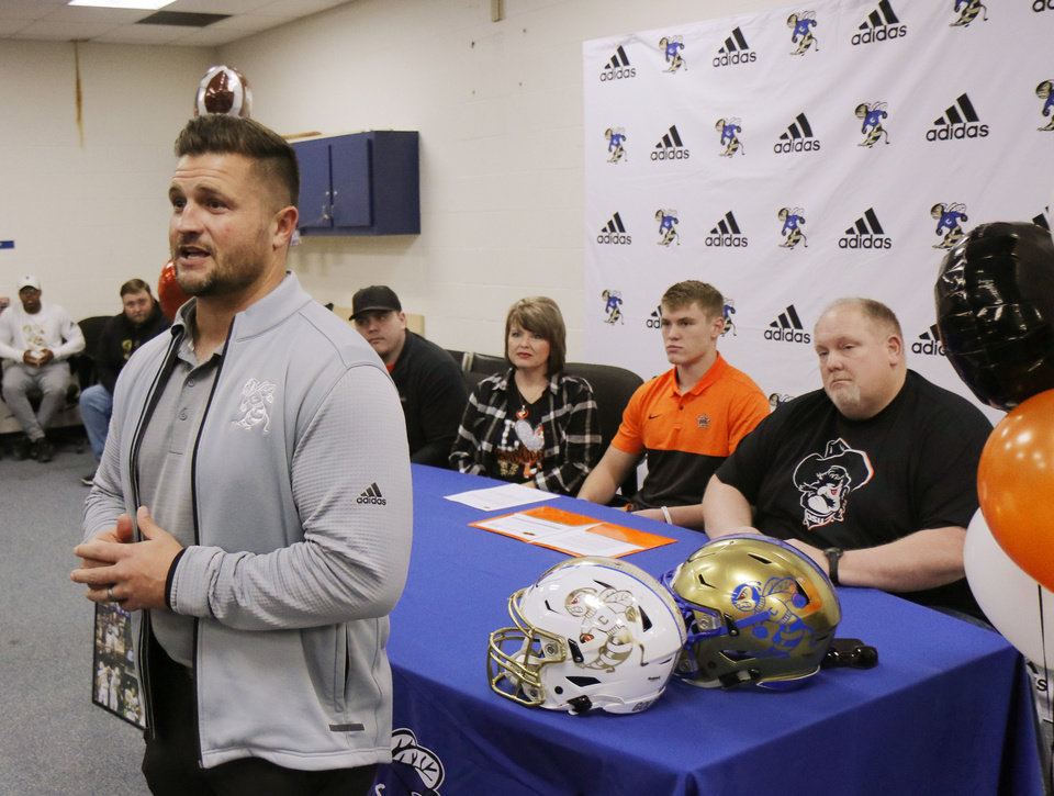 Photo - Choctaw head coach Jake Corbin speaks as brother Logan Roberson, mother DeeDee Devine,  and father Aaron Roberson listen with Jeff Roberson, Choctaw, signs with OSU during National Signing Day for high school football players, Wednesday, December 18, 2019. [Photo by Doug Hoke/The Oklahoman]