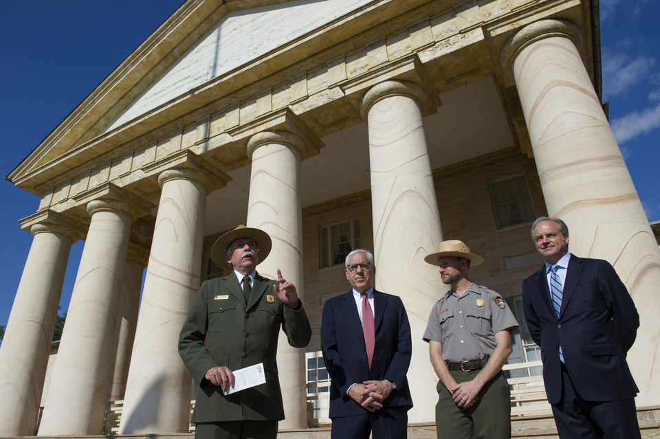 Photo - From left, National Park Service Director Jonathan Jarvis speaks as he is joined by, philanthropist David Rubenstein, Park Ranger Brandon Bies,  and National Park Foundation President and CEO Neil Mulholland,  during a news conference at the Arlington House at Arlington National Cemetery in Arlington, Va., Thursday, July 17, 2014, to announce that the historic house and plantation originally built as a monument to George Washington overlooking the nation's capital that later was home to Confederate Gen. Robert E. Lee and 63 slaves will be restored to its historical appearance after a $12.3 million gift from Rubenstein. (AP Photo/Cliff Owen)