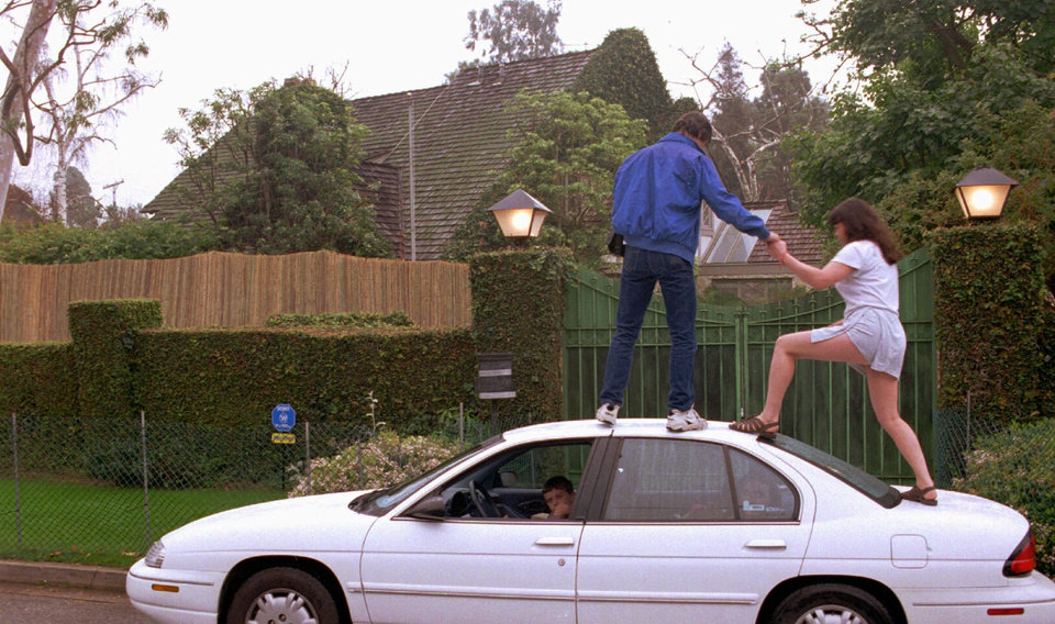 Photo - FILE - In this Feb. 19, 1996 file photo, Guy Cruickshanks and his wife, Kathy, of Canada, climb on top of their car to get a better look at O.J. Simpson's Brentwood home in Los Angeles. The O.J. Simpson spectacle was quickly branded the