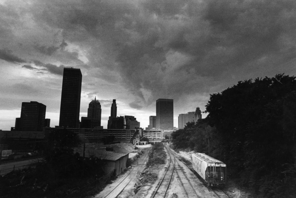 OKLAHOMA CITY / SKY LINE / OKLAHOMA: STORMS CLOUDS HOVER - Low-lying storm clouds loom over downtown Oklahoma City late Monday as scattered thunderstorms rolled across the state. Several streets flooded in the Northwest part of the city during a downpour. More storms are expected today. Staff photo by Paul B. Southerland. Photo dated 06/18/1984 and published 06/19/1984 in The Daily Oklahoman.