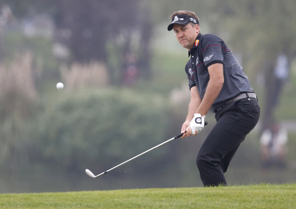 Photo - Early leader and defending champion Ian Poulter of England chips onto the 9th hole during the final round of the HSBC Champions golf tournament at the Sheshan International Golf Club in Shanghai, China, Sunday, Nov. 3, 2013. (AP Photo/Eugene Hoshiko)