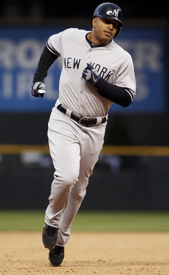 Photo - New York Yankees' Vernon Wells rounds the bases after hitting a two-run home run against the Colorado Rockies in the first inning of a baseball game in Denver on Wednesday, May 8, 2013. (AP Photo/David Zalubowski)