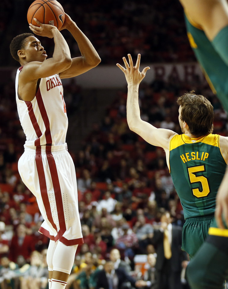 Photo - Oklahoma's Isaiah Cousins (11) shoots against Baylor's Brady Heslip (5) during an NCAA men's college basketball game between Baylor and the University of Oklahoma at Lloyd Noble Center in Norman, Okla., Saturday, Feb. 8, 2014. OU won, 88-72. Photo by Nate Billings, The Oklahoman