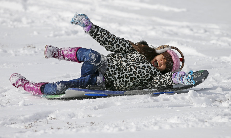 Faith Johnson, 9, screams as she sleds down a hill after a winter storm left a blanket of snow outside her northwest Oklahoma City area neighborhood near 164th and Pennsylvania, Friday, December 6, 2013. Photo by Bryan Terry, The Oklahoman