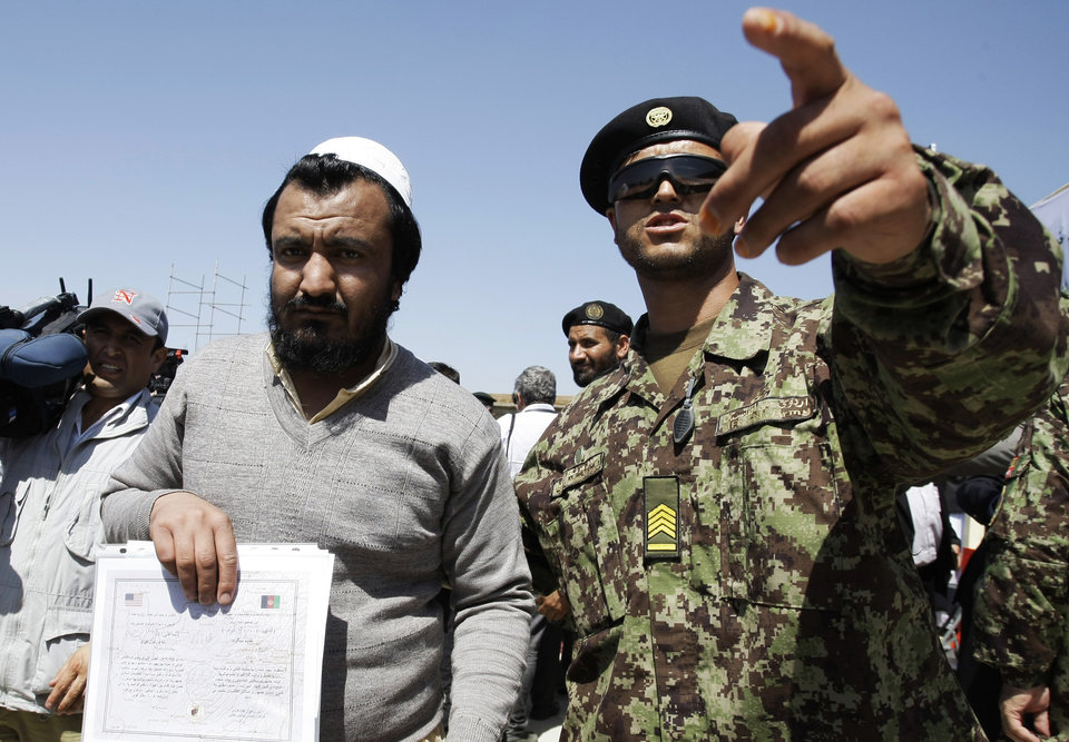 Photo -   An Afghan soldier, right, escorts a released prisoner, Mohammad Karim, following a hand over ceremony of U.S.- run prison to Afghan government in Bagram north of Kabul, Afghanistan, Monday, Sept. 10, 2012. U.S. officials handed over formal control of Afghanistan's only large-scale U.S.-run prison to Kabul on Monday, even as disagreements between the two countries over the thousands of Taliban and terror suspects held there marred the transfer. (AP Photo/Musadeq Sadeq)