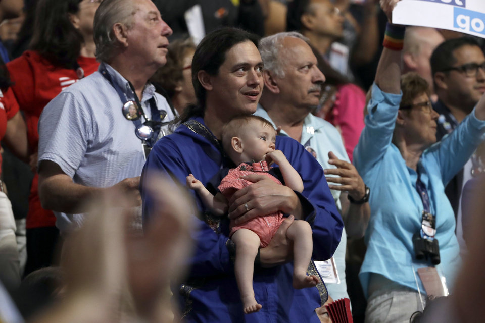 Photo - An Alaska delegate holds his child during the third day session of the Democratic National Convention in Philadelphia, Wednesday, July 27, 2016. (AP Photo/Matt Rourke)