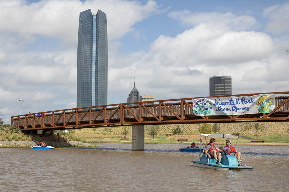 Photo - People ride paddle boats under the skyline of Oklahoma City during the grand opening weekend of Scissortail Park in Oklahoma City, Sunday, Sept. 29, 2019. (Alonzo Adams for The Oklahoman)