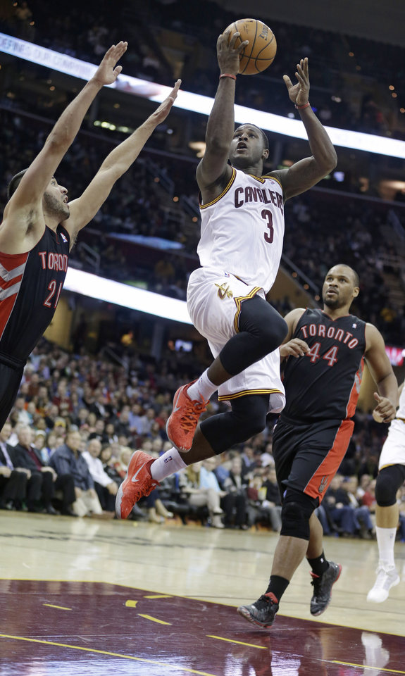 Photo - Cleveland Cavaliers' Dion Waiters (3) jumps to the basket between Toronto Raptors' Greivis Vasquez (21) and Chuck Hayes (44) during the fourth quarter of an NBA basketball game Tuesday, March 25, 2014, in Cleveland. Waiters scored a team-high 24 points for Cleveland's 102-100 win.(AP Photo/Tony Dejak)