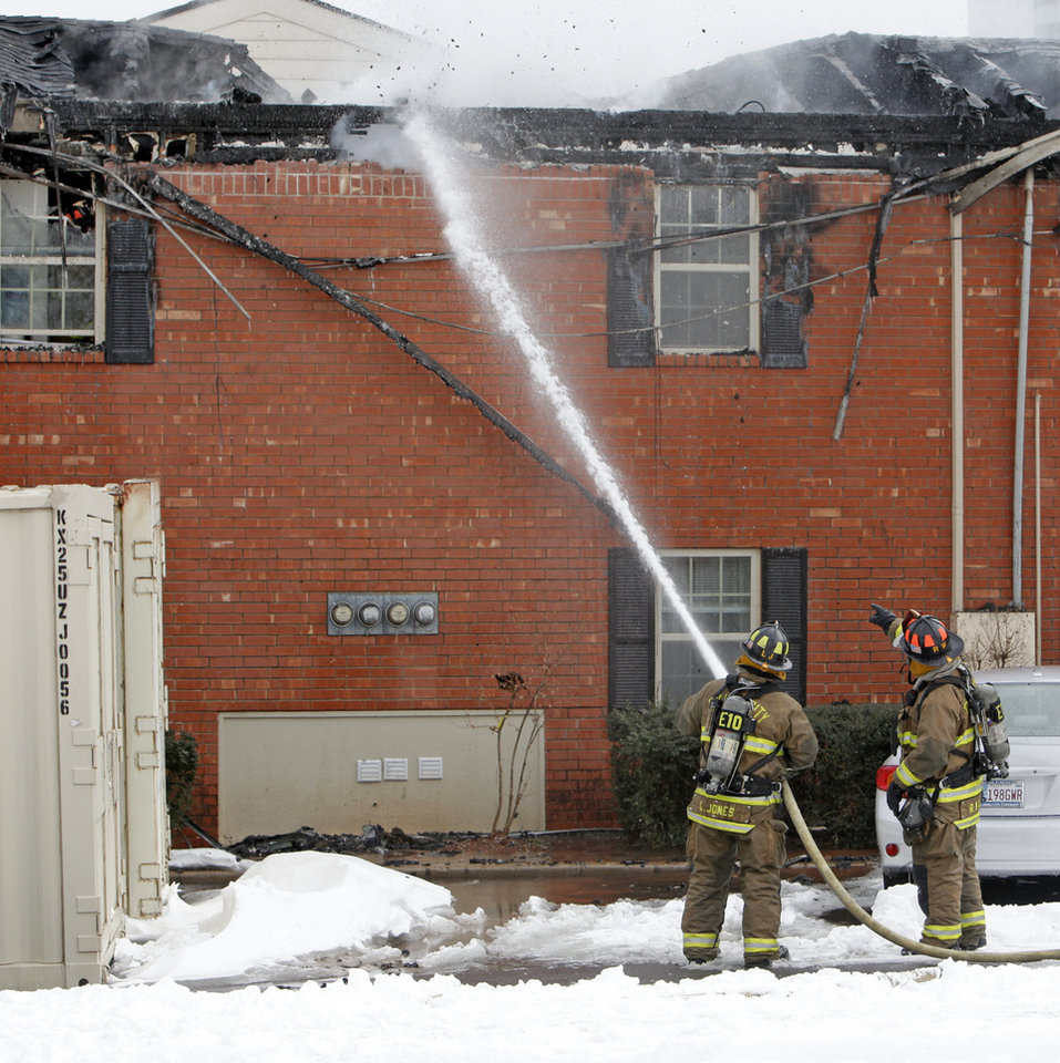 Photo - Oklahoma City firefighters work to put out the remnants of a fire at the Tara Condominiums at NW 62 and Brookline Ave. in Oklahoma City, Thursday, Feb. 3, 2011. Photo by Nate Billings, The Oklahoman