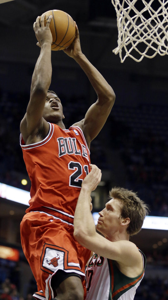 Chicago Bulls' Jimmy Butler, left, puts up a shot over Milwaukee Bucks' Mike Dunleavy, right, during the first half of an NBA basketball game Wednesday, Jan. 30, 2013, in Milwaukee. (AP Photo/Jeffrey Phelps)