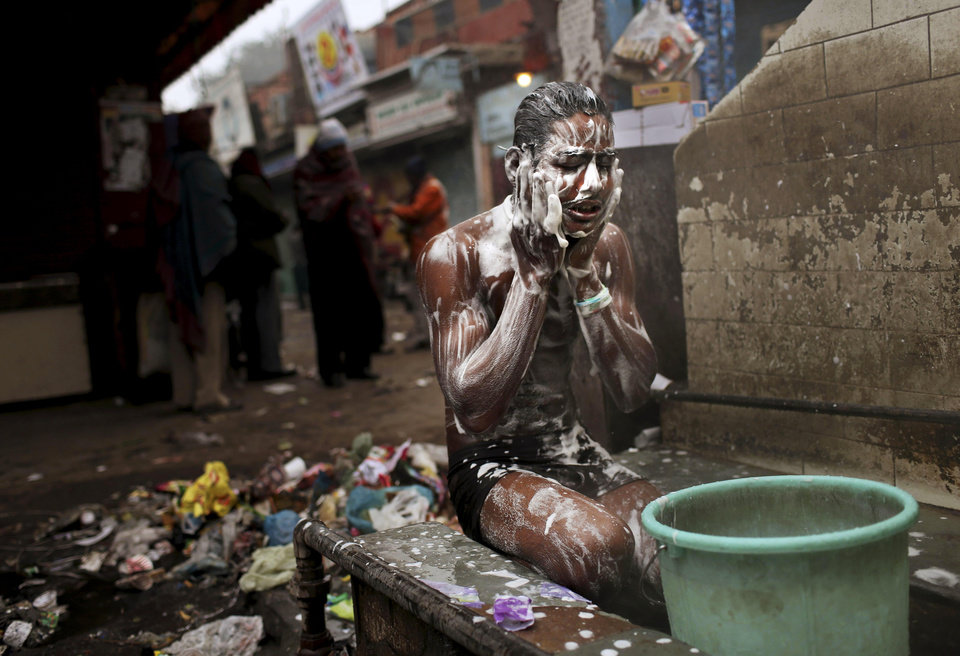 An Indian laborer washes himself at an outdoor tap on a cold winter morning in New Delhi, India, Monday, Jan. 7, 2013. North India continues to face below average weather conditions with dense fog affecting flights and trains. More than 100 people have died of exposure as northern India deals with historically cold temperatures. (AP Photo/Kevin Frayer)