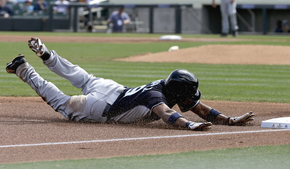 Photo - Seattle Mariners' Endy Chavez steals third base on a over throw against the Arizona Diamondbacks during the first inning of a spring exhibition baseball game, Thursday, March 13, 2014, in Scottsdale, Ariz. (AP Photo/Chris Carlson)