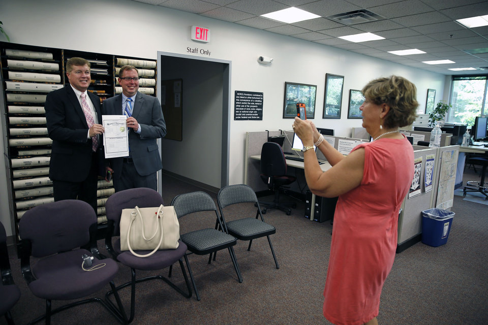 Photo - Longtime same-sex couple Kevin Stalder, far left, and Brad Moses smile for Moses' mother Dianne Lynch to take their picture with their new marriage license, inside the offices of the Boulder County Clerk and Recorder, in Boulder, Colo., Thursday, June 26, 2014. Boulder County Clerk Hillary Hall began issuing licenses a day earlier following a federal appeals court ruling that Utah's same-sex marriage ban is unconstitutional. More couples showed up in Boulder on Thursday to get licenses. (AP Photo/Brennan Linsley)