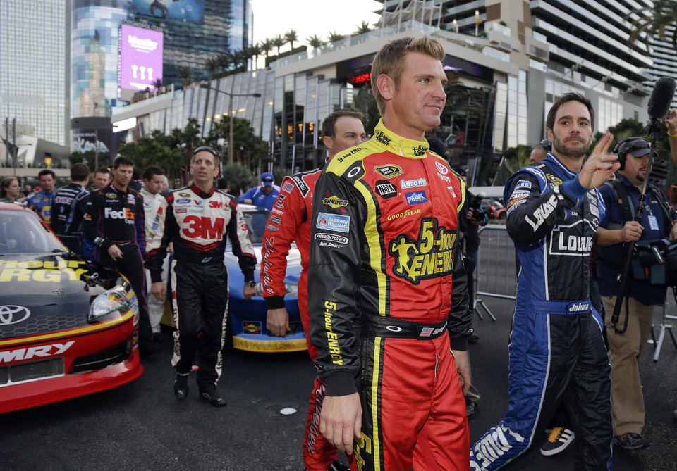 Photo - Clint Bowyer, left, and Jimmie Johnson walk down the Las Vegas Strip after driving in the Nascar Awards Week victory lap, Thursday, Nov. 29, 2012, in Las Vegas. (AP Photo/Julie Jacobson)