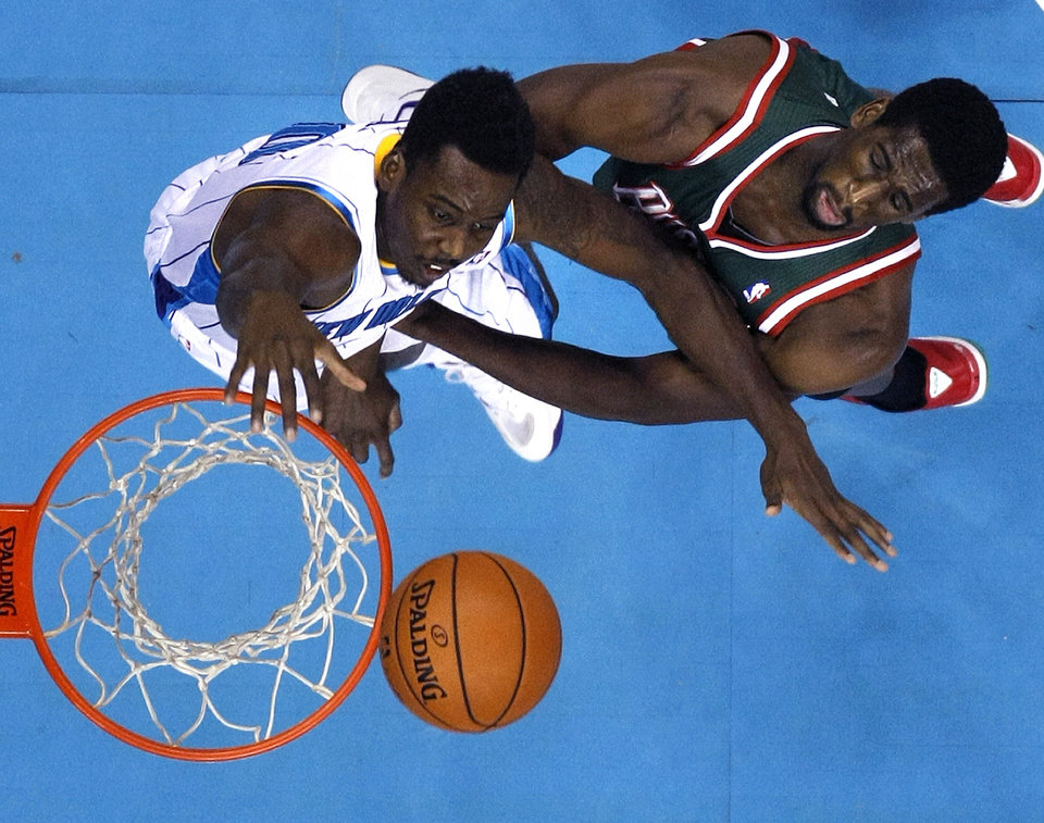 Photo - New Orleans Hornets small forward Al-Farouq Aminu drives to the basket in front of Milwaukee Bucks power forward Ekpe Udoh, right, in the first half of an NBA basketball game in New Orleans, Monday, Dec. 3, 2012. (AP Photo/Gerald Herbert)
