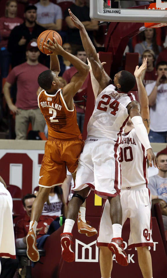 Photo - Oklahoma Sooner Buddy Hield (24) tries to block a shot by Demarcus Holland in the second half as the University of Oklahoma Sooners (OU) men defeat the Texas Longhorns (TU) 77-65 in NCAA, college basketball at The Lloyd Noble Center on Saturday, March 1, 2014  in Norman, Okla. Photo by Steve Sisney, The Oklahoman