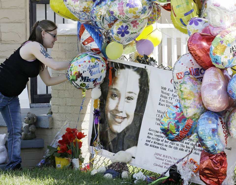 Photo - A girl adds a balloon outside the home of Gina DeJesus Thursday, May 9, 2013, in Cleveland. Ariel Castro, the man accused of raping and kidnapping DeJesus and 2 other women, who were missing for about a decade before being found alive at his home, was ordered held Thursday on $8 million bail. (AP Photo/Tony Dejak)