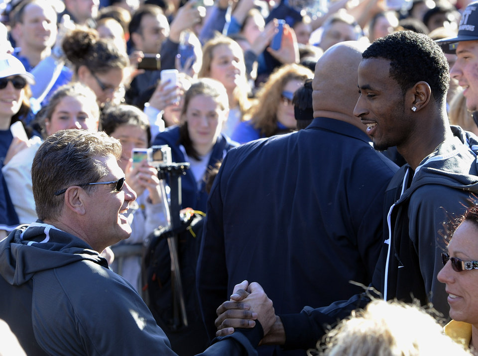 Photo - Connecticut women's basketball coach Geno Auriemma, left, is greeted by Connecticut men's basketball player DeAndre Daniels, right, after Auriemma arrived on campus with his team for a rally celebrating its NCAA championship, Wednesday, April 9, 2014, in Storrs, Conn. (AP Photo/Jessica Hill)