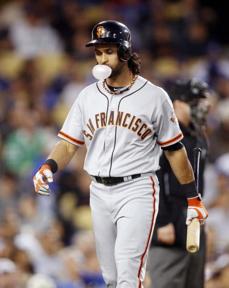 Photo - San Francisco Giants' Angel Pagan blows a bubble and walks back to the dugout after striking out looking against the Los Angeles Dodgers during the third inning of a baseball game, Friday, May 9, 2014, in Los Angeles. (AP Photo/Danny Moloshok)