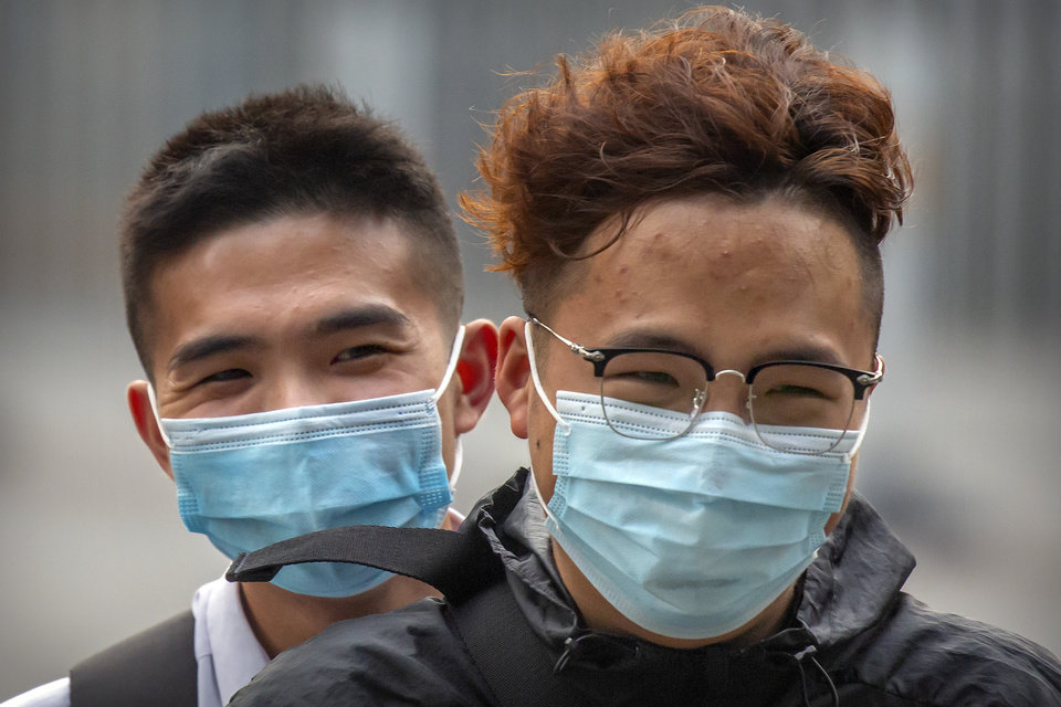 Photo -  People wearing face masks to protect against the coronavirus ride a motor scooter in Beijing, Wednesday, July 29, 2020. China reported more than 100 new cases of COVID-19 on Wednesday as the country continues to battle an outbreak in Xinjiang. (AP Photo/Mark Schiefelbein)