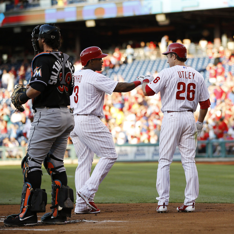 Photo - Philadelphia Phillies' Marlon Byrd, center, and Chase Utley, right, celebrate next to  Miami Marlins catcher Jarrod Saltalamacchia after Byrd's two-run home run during the first inning of a baseball game, Tuesday, June 24, 2014, in Philadelphia. (AP Photo/Matt Slocum)