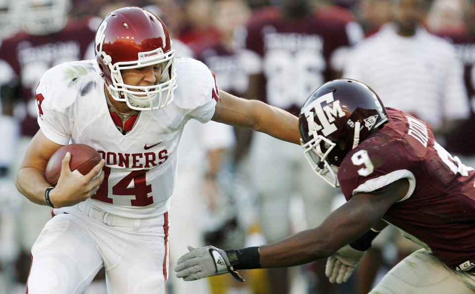 Photo - OU quarterback Sam Bradford stiff arms Alton Dixon of Texas A&M on a keeper late in the second quarter during the college football game between the University of Oklahoma (OU) and Texas A&M University (TAMU) at Kyle Field in College Station, Texas, Saturday, Nov. 8, 2008. The play set up a field goal by the Sooners. BY NATE BILLINGS, THE OKLAHOMAN