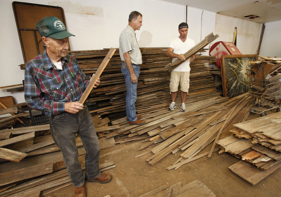 Photo - From left, J. D. Crosby, Wayland Bishop,  and Dan Riedemann among the old boards  that will be used to reconstruct the   Woody Guthrie