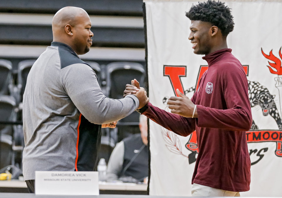 Photo - Westmoore's Damoriea shakes hands with football coach Lorenzo Williams before he signs his letter of intent to play football for Missouri State University during national signing day at Westmoore High School in Moore, Okla. on Wednesday, Feb. 7, 2018.  Photo by Chris Landsberger, The Oklahoman