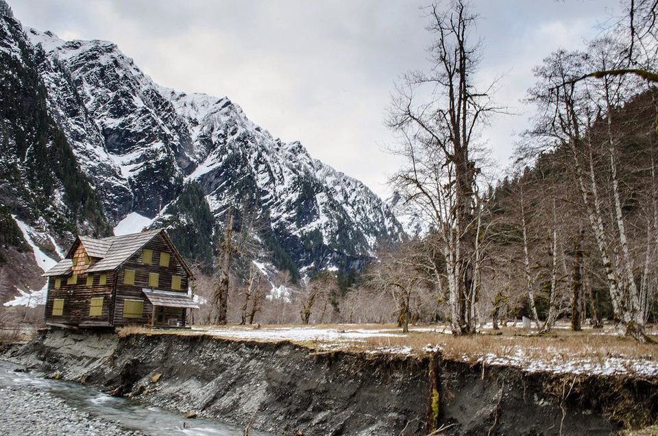 Photo - FILE - In this April 2014, file photo provided by Olympic National Park, the Enchanted Valley Chalet stands on the eroding bank of the Quinault River in Olympic National Park in Washington state. The park says it is moving forward with a plan to move the chalet that is being threatened by the shifting east fork of the river. (AP Photo/Olympic National Park, File)