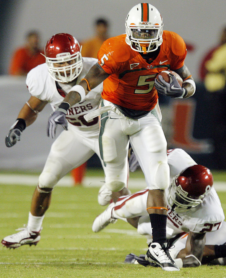 Photo - Miami's Javarris James (5) runs away from OU defenders Travis Lewis (28), left, and Sam Proctor (27), right, during the college football game between the University of Oklahoma (OU) Sooners and the University of Miami (UM) Hurricanes at Land Shark Stadium in Miami Gardens, Florida, Saturday, October 3, 2009. Miami won, 21-20. Photo by Nate Billings, The Oklahoman